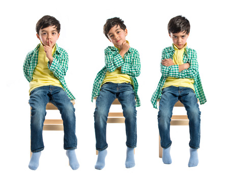 Boy thinking on wooden chair over white background photo