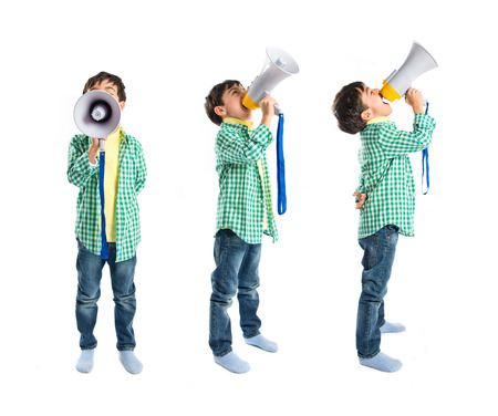 Kid shouting by megaphone over white background  photo