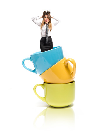 Businesswoman frustrated inside colorful cups over white  photo