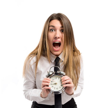 Young businesswoman holding an antique clock over white background  photo