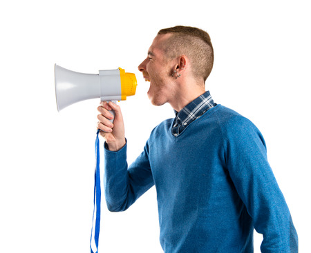 Redhead man shouting by megaphone over white background  photo
