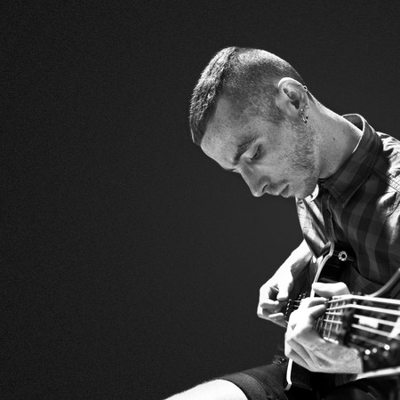 Young man playing guitar over black background photo