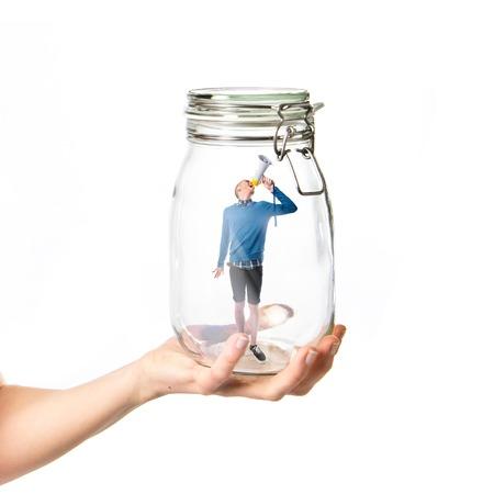 Man shouting by megaphone inside glass jar photo