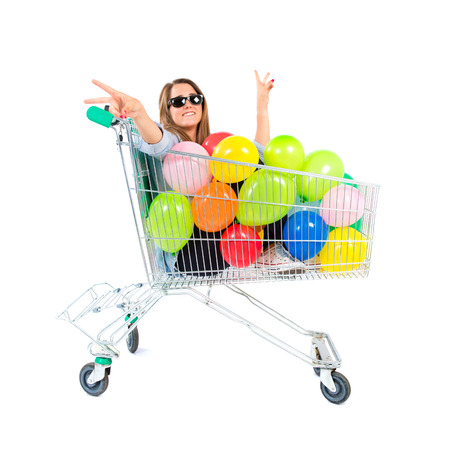 Girl with many balloons inside supermarket cart over white background photo
