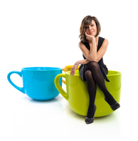 Pretty brunette woman with black dress sitting on coffee cup  photo
