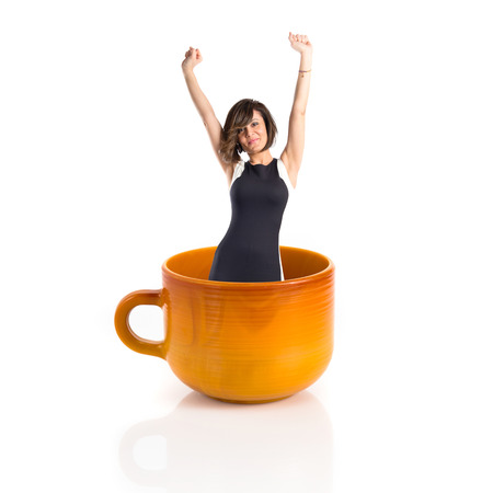 woman handle success: Woman inside ceramic cup over white backgrpund