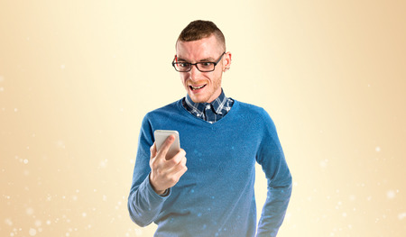Young shouting to mobile over yellow background.  photo