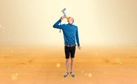 criticizes: Redhead man shouting by megaphone over ocher background  Stock Photo