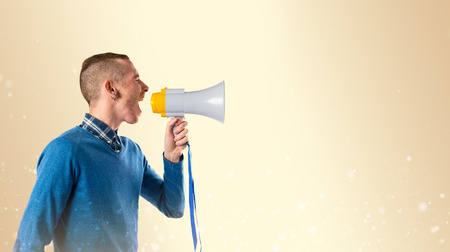 criticizes: Redhead man shouting by megaphone over yellow background