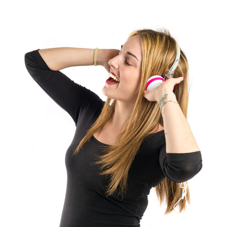 Young blonde girl listening music over white background  photo