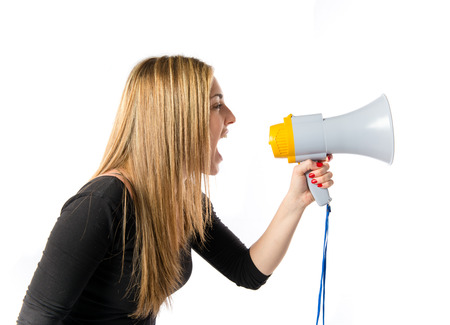 Pretty girl shouting with a megaphone over white background  photo