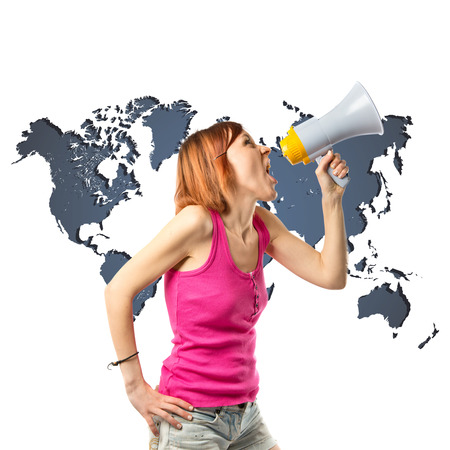 Redhead girl shouting with a megaphone over white background  photo