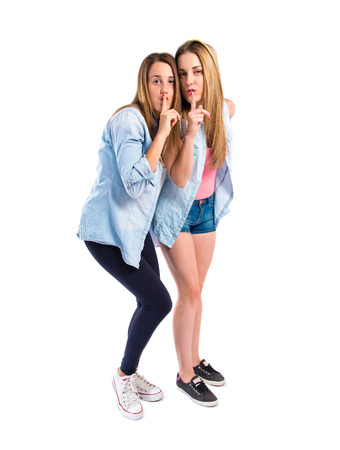 Friends making silence gesture over isolated white   photo