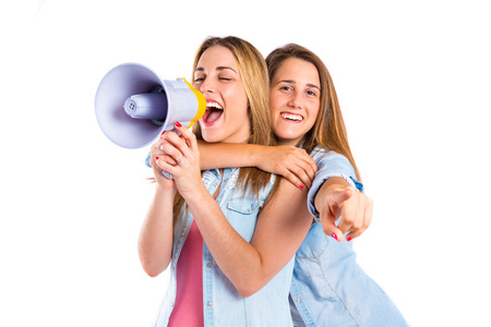 Girls shouting with megaphone over white  photo