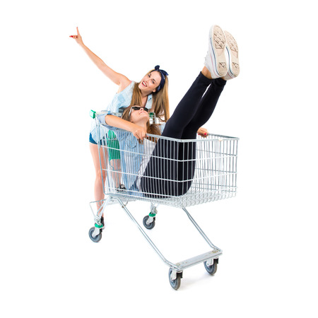 Girl inside supermarket cart with her sister photo