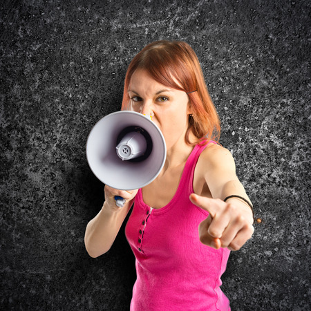 Redhead girl shouting with a megaphone over black  photo
