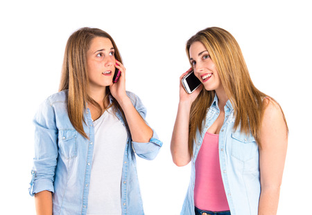 Young girls talking to mobile over white  photo