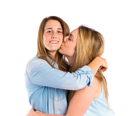 Girl giving kiss at her sister over white  photo