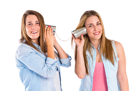 Friends talking through a tin phone over white  photo