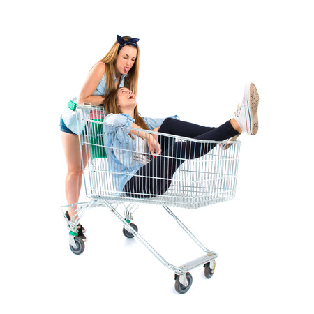 Girl inside supermarket cart over white  photo