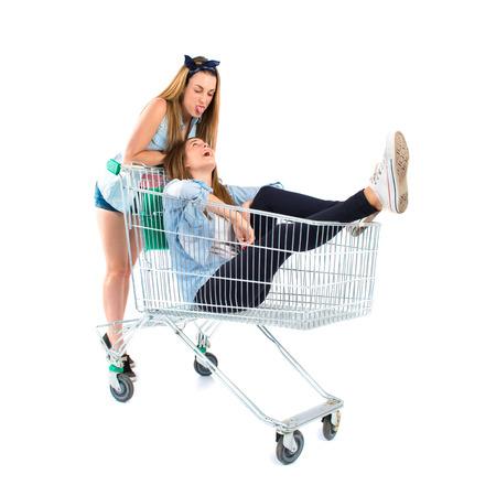 Girl inside supermarket cart over white  photo