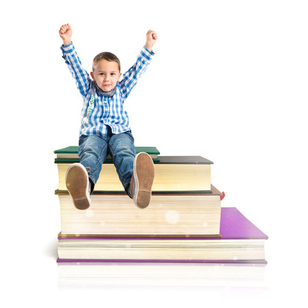 Kids on several books isolated over white  photo