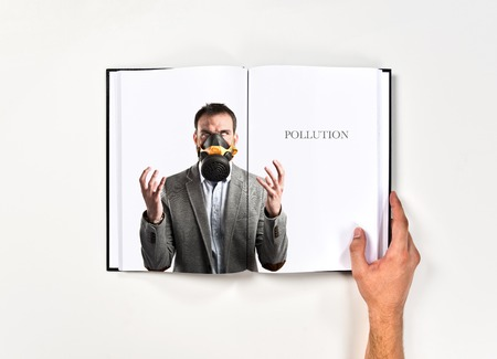 young businessman with gas mask printed on book photo