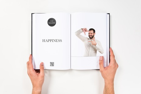 Young man doing a frame sign printed on book photo