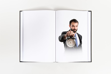 Young businessman holding an antique clock printed on book photo