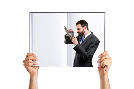 Young businessmen smelling his shoes printed on book photo