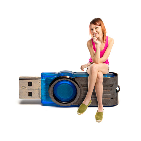 Redhead girl sitting on pendrive over white background  photo