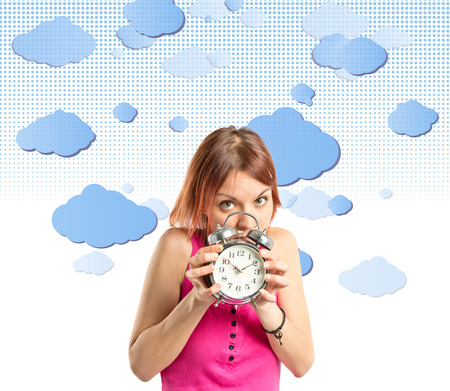 Serious redhead girl holding a clock over sky background  photo