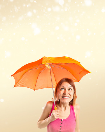 Girl holding an umbrella over ocher background photo