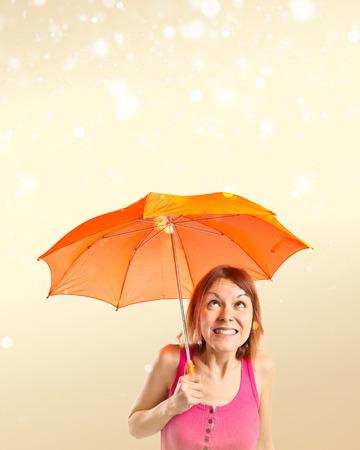 Girl holding an umbrella over ocher background photo