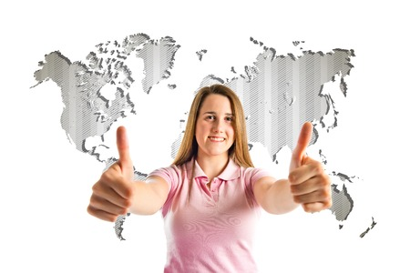 Young girl making Ok sign over atlas background  photo
