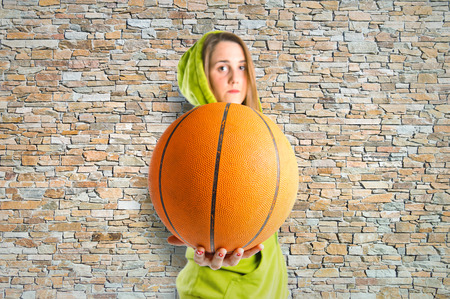Blonde girl playing basketball over texture background photo