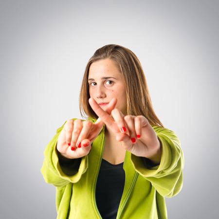 comunicacion no verbal: Chica haciendo ningún gesto sobre fondo gris