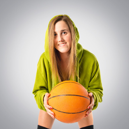 Blonde girl playing basketball over grey background photo