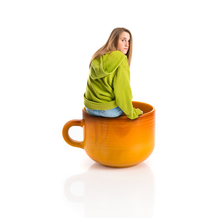 Pretty young girl wearing urban style inside cup of coffee photo