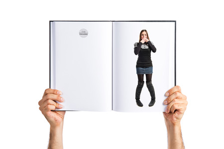 Pretty young girl with her mouth closed by her hands printed on book photo