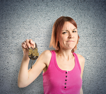 Redhead girl holding vintage padlock over textured background  photo