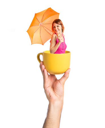Girl holding an umbrella inside cup of coffee photo