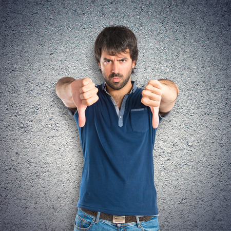 Man doing a bad signal over textured background photo
