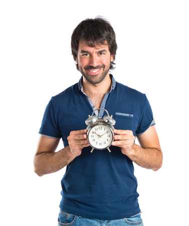 Man holding a clock over white background photo