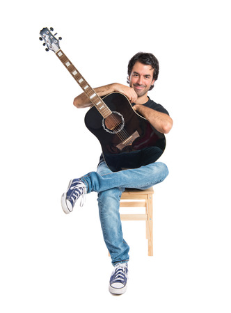 Handsome man with guitar over white background photo
