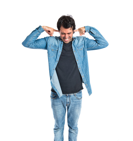 Man covering his ears over white background photo