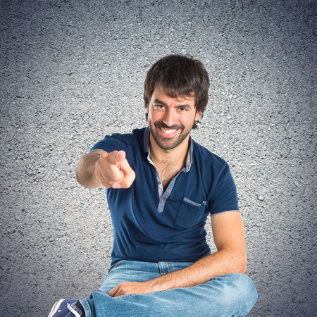 Man pointing to the front over textured background photo