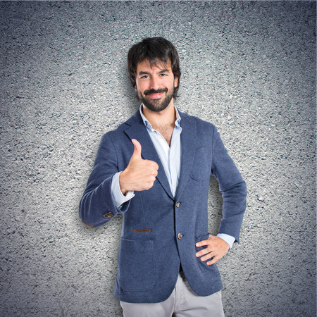 Handsome man with thumb up over textured background photo