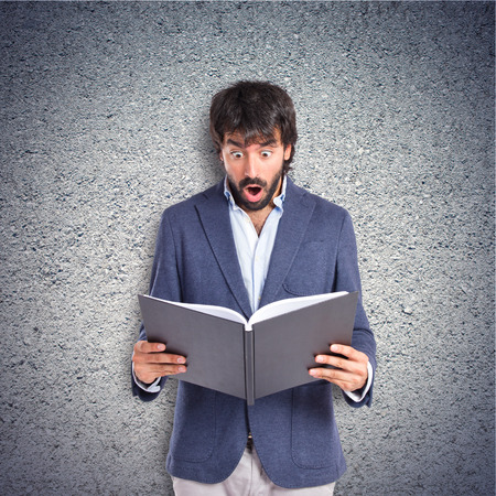 Surprised man reading a book over textured background photo