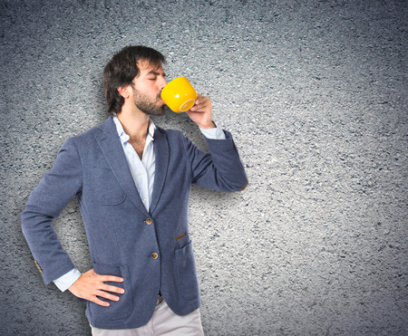Businessman holding a cup of coffee over textured background photo